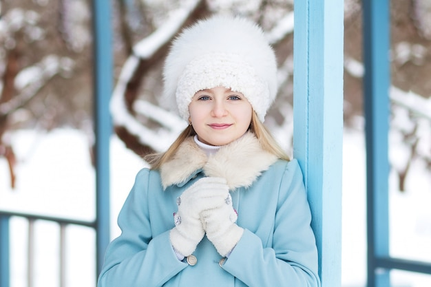Cute blonde girl in a blue coat and white fur hat in winter. snowy weather. the girl on the porch of the house.  the concept of winter holidays. close-up portrait of a blonde girl's face.