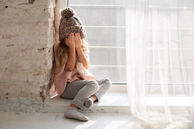 Cute blonde girl covering her face