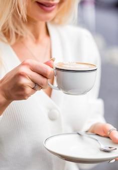 Милая блондинка девушка держит блюдце, чашку капучино и улыбается. фото