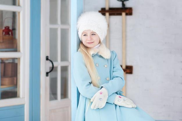 冬の青いコートと白い毛皮の帽子でかわいいブロンドの女の子。雪の天気。家のポーチの女の子。冬の家。路上でポーズをとるモデル。冬の休日の概念。