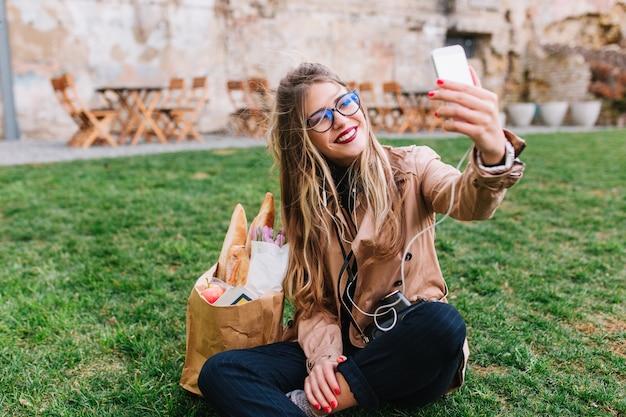 公園の緑の芝生の上に座って手でselfieを作るガラスのかわいいブロンドの女の子。買い物を終えて休憩を取って、足を組んでinstagramプロファイルの写真を作る魅力的な若い女性