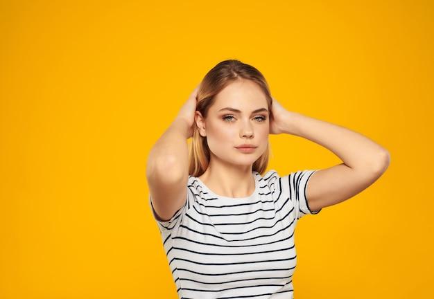 縞模様のtシャツのかわいいブロンドの女の子楽しい魅力的な外観黄色の背景