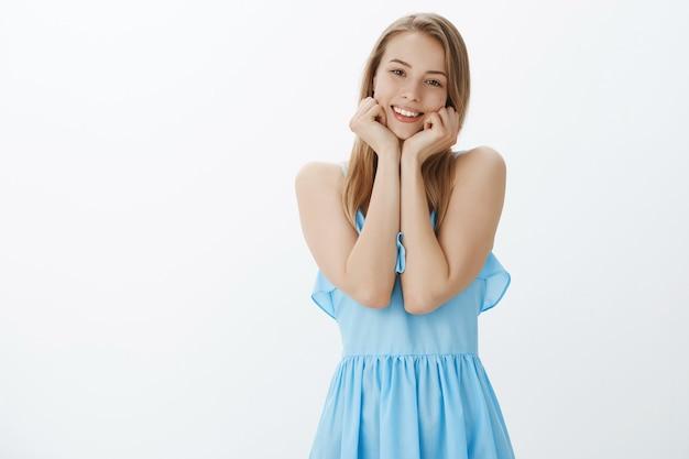 スタイリッシュな青いドレスのかわいいブロンドの女の子