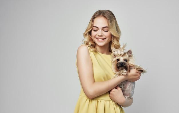 純血種の犬のポーズで黄色のドレスを着たかわいいブロンドの女の子。