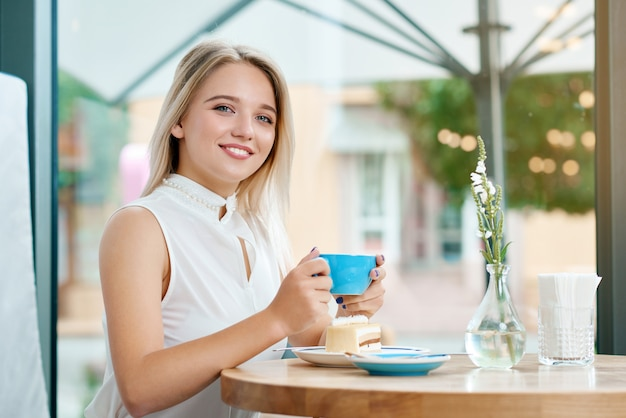 Cute blonde girl keeping cup of coffee on outdoors, smiling.