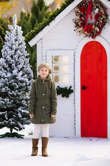 Cute blonde girl near the small house and snow-covered trees. new year and christmas time