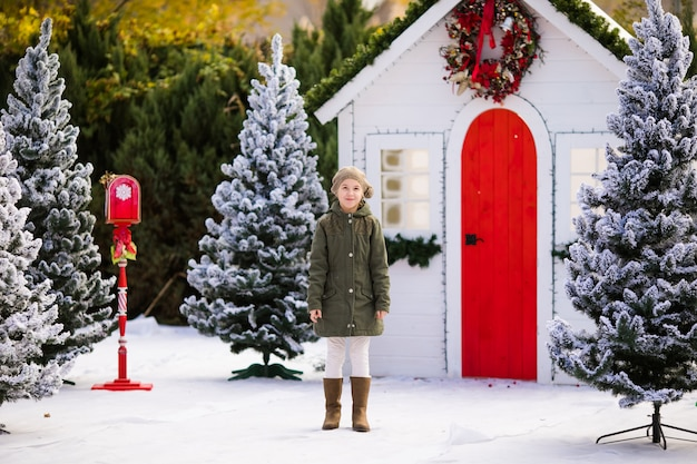 Cute blonde girl near the small house and snow-covered trees