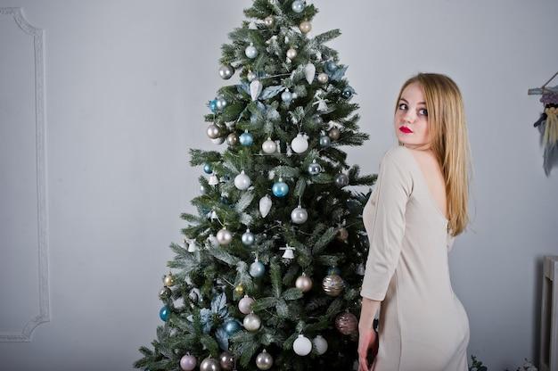 クリスマスツリーに対してベージュのドレスでかわいいブロンドの女の子。
