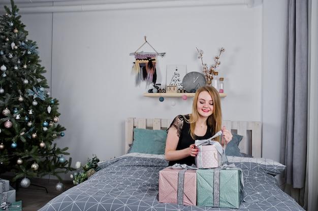 クリスマスツリーに対してギフトボックスでベッドに横になっている黒のドレスでかわいいブロンドの女の子。