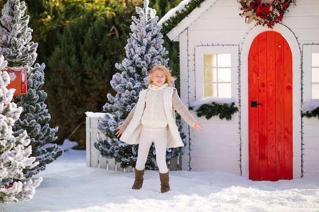 Cute blonde girl playing with snow near the small house and snow-covered trees