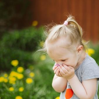 かわいいブロンドの女の子は、庭の花の一握りを嗅ぎます。