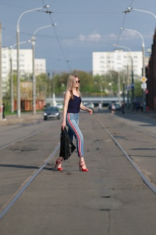 Cute blonde girl in sunglasses crossing the road with leather jacket in hand