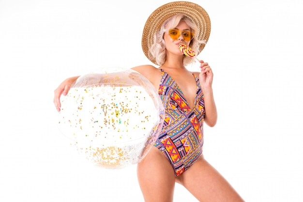 Cute blonde girl in a swimsuit in sunglasses holds a lollipop and a swimming ball