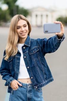 야외에서 자기 사진을 복용 귀여운 금발 소녀