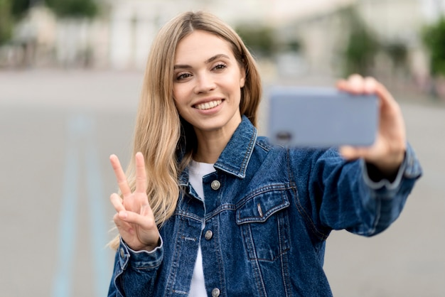 Cute blonde girl taking a selfie peace sign