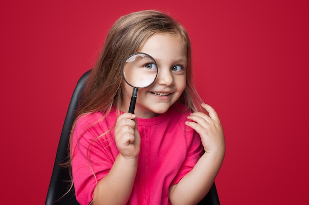 Cute blonde girl using a magnifier glass while looking for something and smile on a red studio wall in armchair
