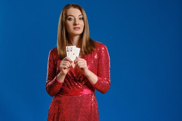 Милая блондинка с макияжем, в красном платье с пайетками показывает две игральные карты, позирует на синем фоне. азартные развлечения, покер, казино. крупный план.