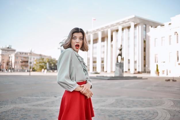 散歩のポーズをとって街の屋外で赤い唇を持つかわいいブロンドの女の子