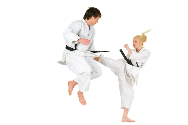 Cute blonde girl and a young cheeky guy karate are engaged in training in a kimono on a white