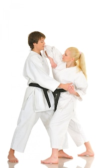 Cute blonde girl and a young cheeky guy karate