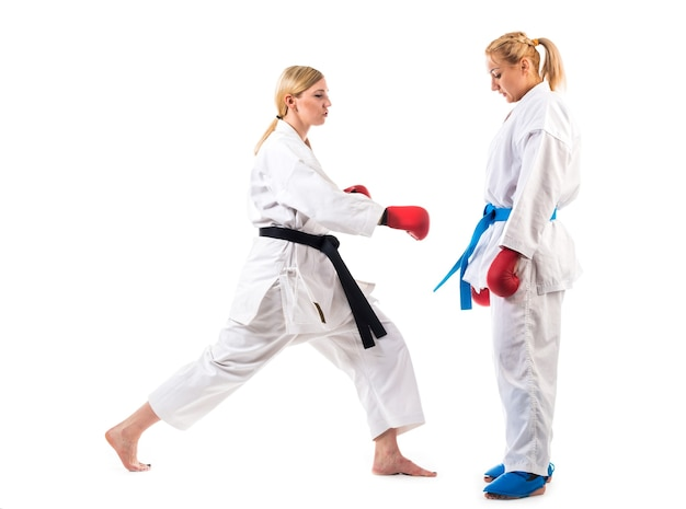 귀여운 금발 소녀 가라테는 흰색 배경에 기모노 훈련에 종사하고 있습니다. 성능을 위해 준비하는 선수의 젊은 부부.
