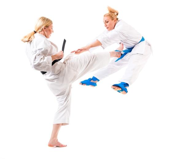 かわいいブロンドの女の子空手は、白い背景の上の着物のトレーニングに従事しています。