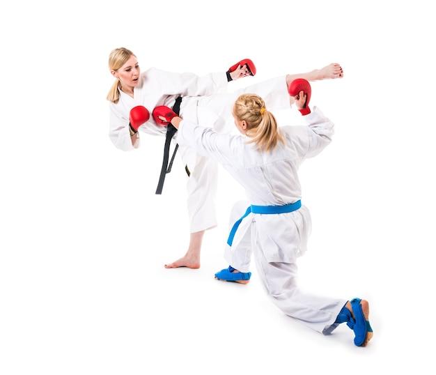 かわいいブロンドの女の子空手は白い壁の着物で訓練に従事しています