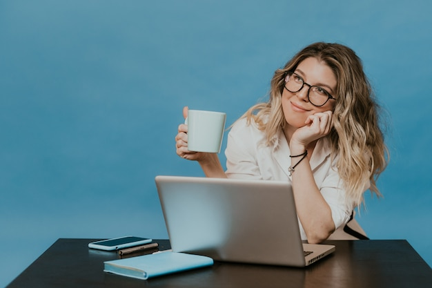 Cute blonde in glasses holding a cup of coffee, sitting at the table with laptop, looking dreamily aside, thinking about vacations and parties after the self-isolation ends. covid-19 pandemic concept.