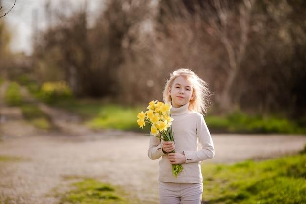 Симпатичная белокурая счастливая маленькая девочка с желтыми нарциссами в весенней стране