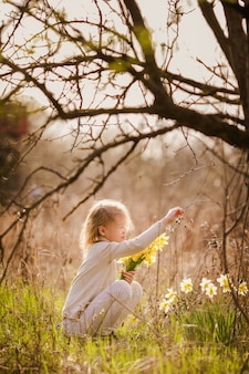 Cute blonde happy little girl with yellow daffodils in the spring country