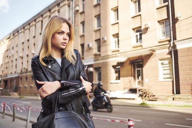 黒いジャケットのかわいいブロンドは、屋外でライフスタイルを歩きます。高品質の写真