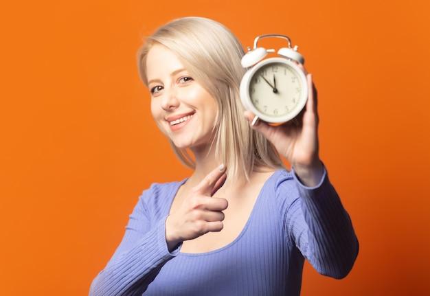 鮮やかなオレンジ色の背景に青いブラウスと目覚まし時計のかわいいブロンド