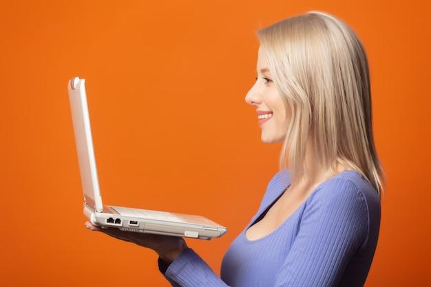 Милая блондинка в синей блузке с портативным компьютером на ярком оранжевом фоне