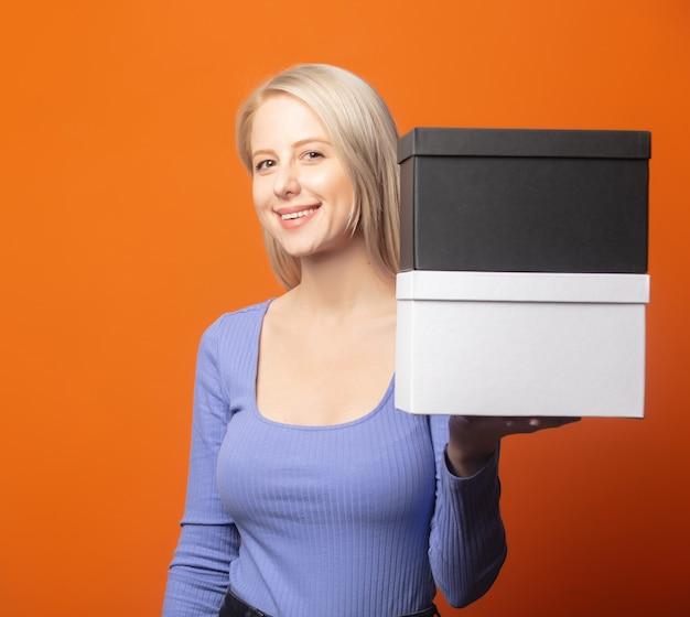 Милая блондинка в синей блузке с двумя подарочными коробками на ярком оранжевом фоне