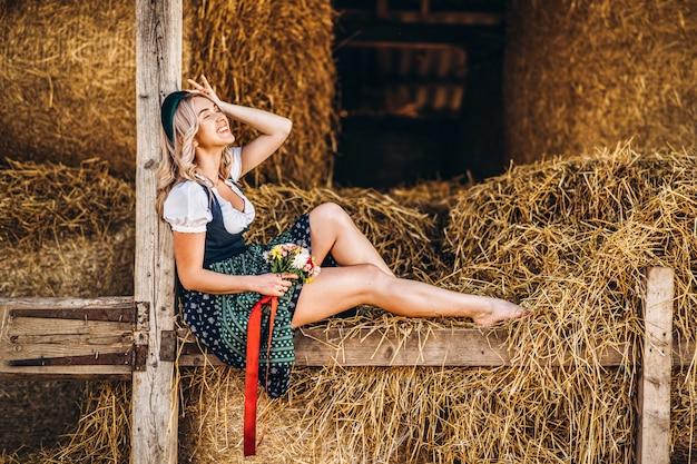 Симпатичная блондинка в дирндль, традиционное праздничное платье с букетом полевых цветов сидит на деревянном заборе на ферме