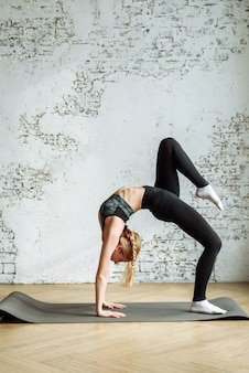 Cute blonde is engaged in fitness on the background of a white brick wall at home