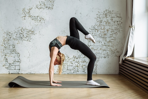 Cute blonde is engaged in fitness on the wall of a white brick wall at home during quarantine