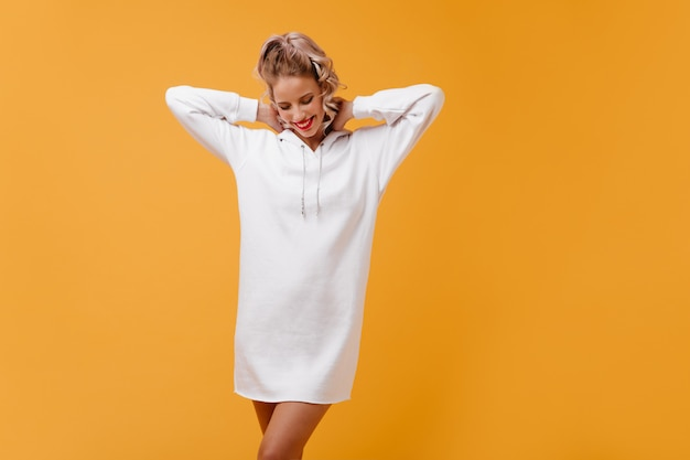 Cute blonde is relaxing in long sports sweater