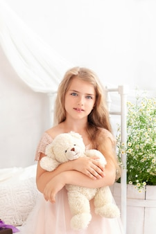 Cute blonde little girl in dress hugs teddy bear on bed in bedroom at home. child playing a toy.
