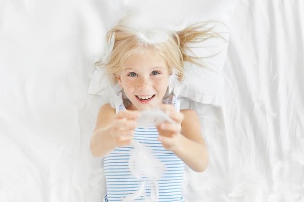 침대에서 귀여운 금발 소녀