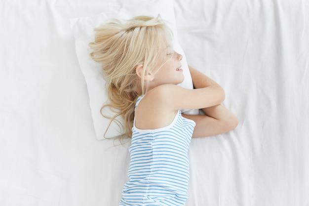 흰색 침대에 귀여운 금발 소녀