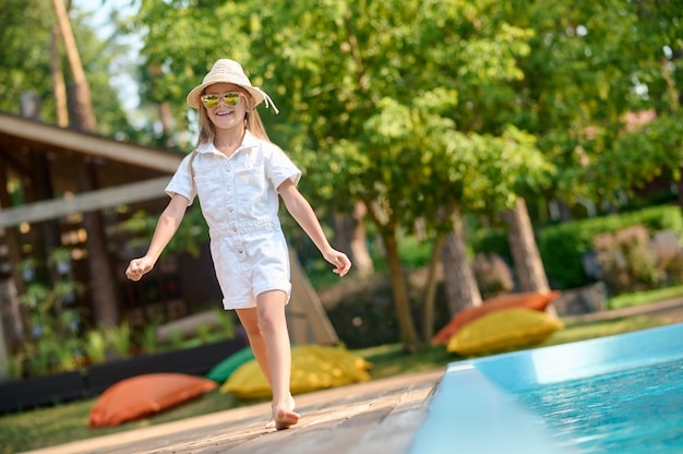 A cute blonde little girl near the swimming pool