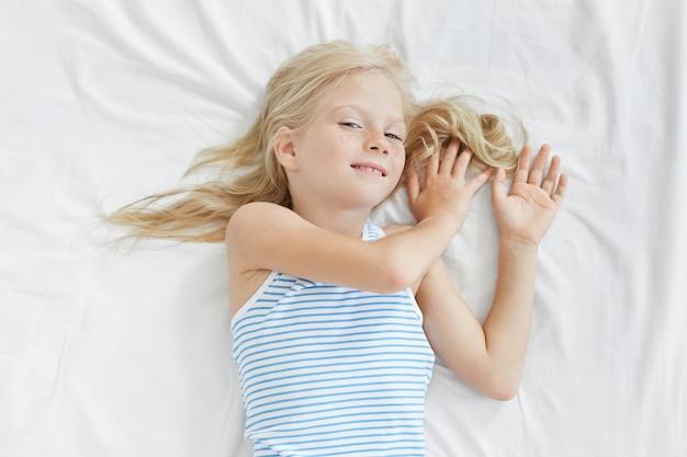 白いベッドでストレッチかわいい金髪の女の子