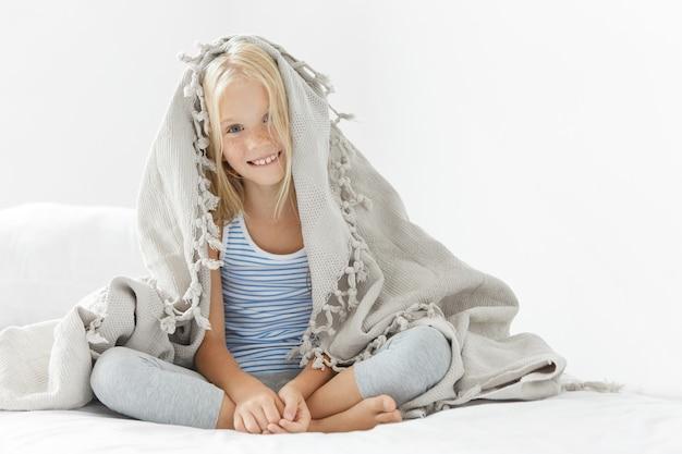 Милая блондинка маленькая девочка под одеялом