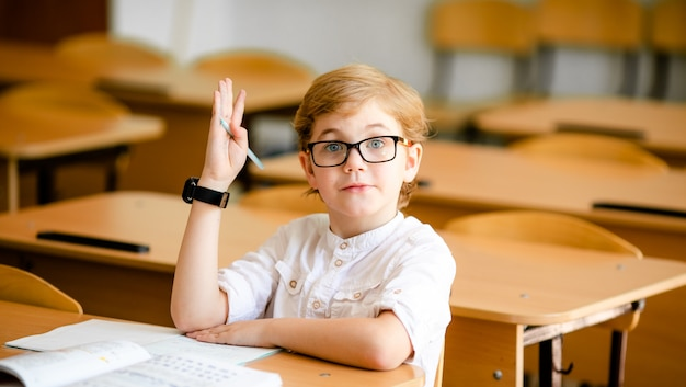 Cute blonde school student with stylish glasses writing in classroom