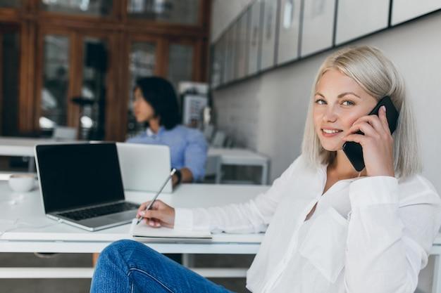 Милая блондинка секретарь в белой блузке разговаривает по телефону и записывает данные в записную книжку. внутренний портрет длинноволосого азиатского ит-специалиста с изящной дамой на стойке регистрации.