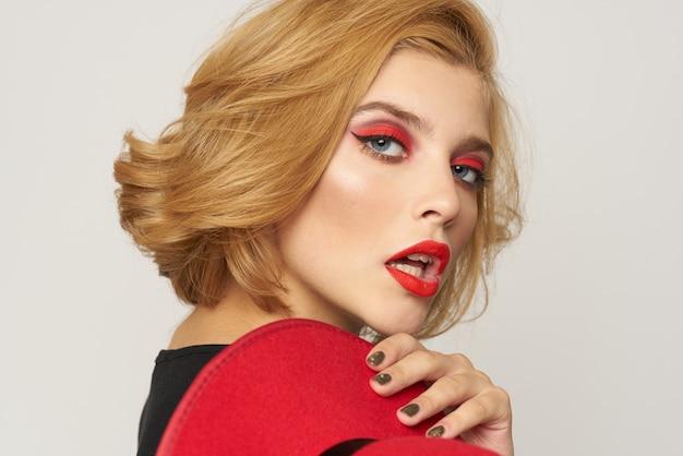 かわいい金髪の短い髪の赤い帽子を手にクローズアップ明るい背景。