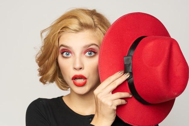 手にクローズアップライトでかわいい金髪の短い髪の赤い帽子。高品質の写真