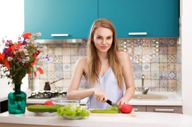 青いキッチンの背景にかわいい金髪スライスサラダ用野菜