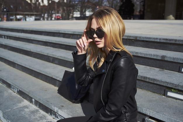 Cute blonde in sunglasses outdoors walk street style. high quality photo